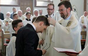 Provinzial Pater Reinhard Gesing legt Mike Goldsmits das Professkreuz als äußeres Zeichen seiner Zugehörigkeit zur Ordensgemeinschaft der Salesianer Don Boscos an. Foto: Salesianer