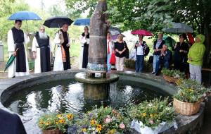 Mönche und kfd-Mitglieder versammelten sich zur Kräutersegnung am Brunnen.