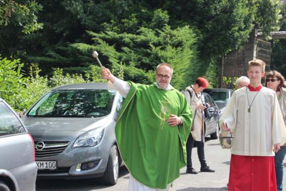 Pater Felix Rehbock segnet am Nikolauskloster wieder Fahrzeuge vor den Sommerferien.