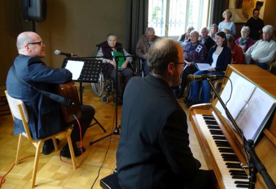 """Bürgermeister Klaus Krützen an der Gitarre und Kulturamtsleiter Stefan Pelzer-Florack am Klavier singen mit den Senioren """"Kein schöner Land""""."""