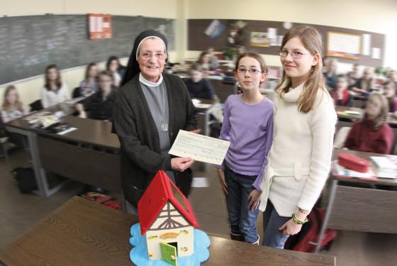 Schülerinnen des Gymnasiums Marienberg überreichen Schwester Mechthild einen Scheck in Höhe von 813,18 Euro im Klassenraum.