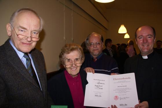 Msgr. Guido Assmann überreicht die Urkunde an die Eheleute Schmidt, im Hintergrund KÖBAG-Vorsitzender Manfred Berdel